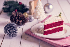 Christmas cake on plate on red fabric on wood background and dec Stock Image