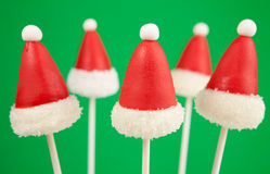 Christmas cake pops. Santa Claus hat cake pops. Mini cakes on stick dipped in chocolate and decorated with fondant Royalty Free Stock Photo