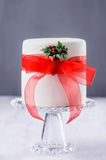 Christmas cake with red ribbon and mistletoe on grey background Royalty Free Stock Photo