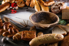 Christmas cake, rolls and breads on wooden table with wooden bowl, background for bakery or market Royalty Free Stock Images