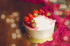 Christmas cake with strowsberry raspberry chocolate. And lights bokeh homemade bakery on wooden background Stock Images