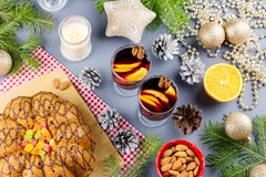 Christmas cake, two glasses of hot mulled wine with sliced orange. Christmas background with food and decorations. Top view royalty free stock images