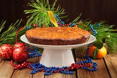 Christmas cake on white plate with fur tree, tangerine and chris. Tmas toys on wood table Stock Images