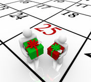 Christmas Calendar -  People Exchanging Gifts. Two people stand on a calendar marked for Christmas, December 25, and exchange holiday presents Royalty Free Stock Image