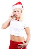 Christmas calling. Beautiful woman  in a santa's cap cell phone. Isolated on white background Royalty Free Stock Image