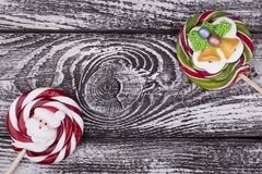 Christmas candies on wooden background. Lollipops with Santa and Christmas bells. Sweet gift for the holiday stock image