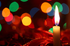 Christmas Candle. Glowing against red ribbons and defocused fairy lights Royalty Free Stock Images