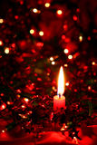 Christmas Candle. Glowing in the darkness, with fairy lights and decorations Stock Photo