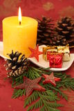 Christmas candle. And decorations on a red background Royalty Free Stock Photos