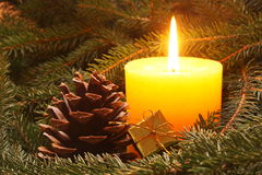 Christmas candle. Yellow candle and small gift in a needles Stock Image