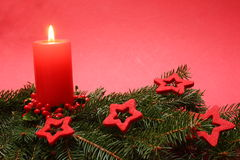 Christmas candle. On a red background Royalty Free Stock Images