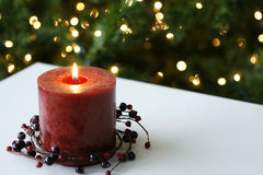 Christmas Candle. Single red candle lit at christmas time Stock Image