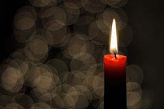 Christmas Candle. A red candle with a Christmas lights background Royalty Free Stock Photography