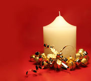 Christmas Candle. White church candle with gold bells on red background for Christmas royalty free stock image