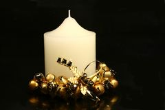Christmas Candle. White church candle with gold bells on black background for Christmas royalty free stock photography