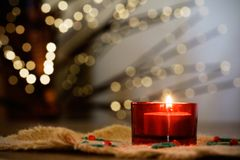 Christmas candle. Red christmas candle, blurry christmaslights on background Royalty Free Stock Photography