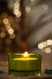 Christmas candle. Green christmas candle, blurry christmaslights on background Royalty Free Stock Photos