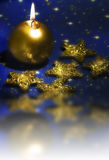 Christmas candle. A gold candle with gold stars over blue Christmas background with reflecting effect Stock Photography