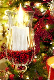 Christmas candle. A white decorative holiday christmas candle burns in a glass holder with pine and red decorations of a christmas tree in the background Stock Image