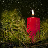 Christmas candle. Burning red candle amongst green fir branches, sparkling stars in the background; Christmas concept Royalty Free Stock Images