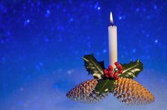 Christmas candle. Christmas image of candle, pine cones and holly on blue background with defocused snowflakes Royalty Free Stock Photography