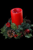 Christmas Candle. Lighted red Christmas candle with wreath base, black iso Stock Photos