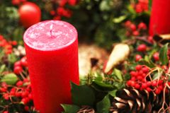 Christmas Candle. A Red Christmas Candle with Pine cone and holly decorations Royalty Free Stock Image