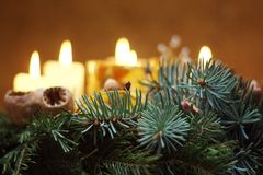 Christmas candle. Christmass chain with cones, Golden tree with gems and gell candle full of star anise stock images