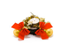 Christmas candle with balls and bows on white. A christmas candle with yellow balls and red bows Royalty Free Stock Image