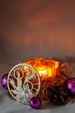 Christmas Candle. Among Christmas balls, cones, decorative ornaments from wood Royalty Free Stock Photography