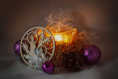 Christmas Candle. Among Christmas balls, cones, decorative ornaments from wood Stock Photo