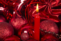 Christmas candle and balls in red tone. Royalty Free Stock Images