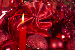 Christmas candle and balls in red tone. Royalty Free Stock Photo