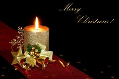 Christmas candle on a black background. New Year card. Burning candle with Christmas decorations Stock Image