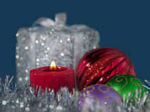 Christmas candle burning in the middle of tinsel Royalty Free Stock Photo