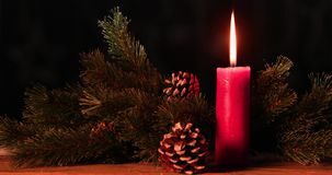 Christmas candle burning on the wooden table