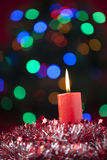 Christmas candle with colorful lights background Royalty Free Stock Photos