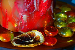 Christmas candle ornaments. Detail of the bottom of a colorful candle decorated with glass marbles and a dried orange slice Stock Images