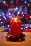 Christmas candle and decorated tree background. Stock Photos