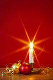 Christmas candle and decorations. A lit candle in brass holder with Christmas decorations and red background, star filter used during capture for the flame. Copy Royalty Free Stock Photo