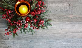 Christmas Candle with Evergreen Tree Branches and Berries Over Rustic Wood stock image