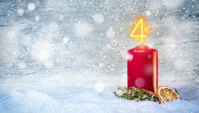 4th Advent candle with snow. Christmas candle with a flame in shape of the number 4. Decorative background with snowflakes, cinnamon and a dried orange slice Royalty Free Stock Photo
