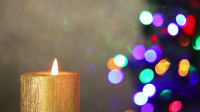 Christmas candle in front of christmas tree stock footage
