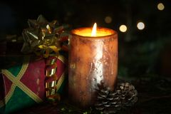 Christmas candle with gift and lights. Royalty Free Stock Photo