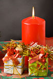 Christmas candle and gifts. Two little xmas gifts with typical decorations and a red xmas candle Stock Images