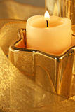 Christmas Candle Gold. Christmas candle and star-shape holder in gold with gold sheer ribon stock image