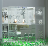Christmas candle and green tinsel with sequins. The deer on the glass background Stock Photos