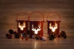 Christmas candle holders with pine cones on wooden background Stock Images