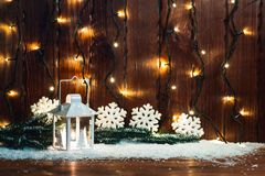 Christmas candle lantern and Christmas tree branches, snow, snowflake and decorations on bokeh background blurred lig. Hts. Free space Royalty Free Stock Photos