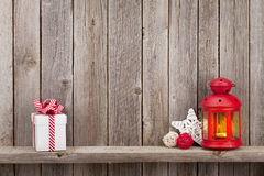 Christmas candle lantern, gift and decor. Christmas candle lantern, gift box and decor in front of wooden wall with copy space Royalty Free Stock Photography